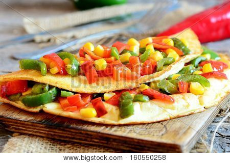 Stuffed omelette on a wooden board. Healthy fried omelette stuffed with red and green bell peppers and corn. Quick breakfast omelet recipe. Rustic style. Closeup