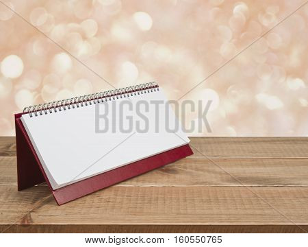 Blank desk calendar diary on wooden table over abstract background