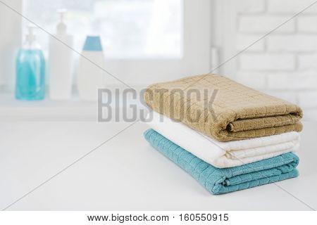 Bath towel pile on wood over defocused bathroom windowsill background
