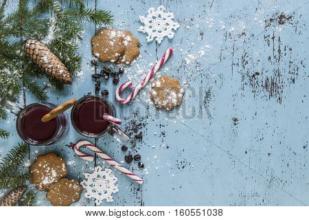 Christmas background with mulled wine, gingerbread, candy cane and fir tree decoration. Old blue wooden table.
