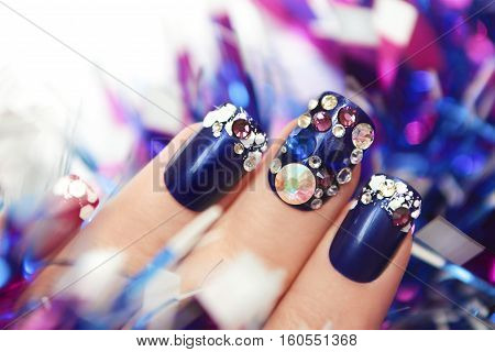 Christmas winter blue manicure with rhinestones of different shapes and sparkles of snow on female hand with a garland.
