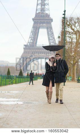 Couple Walking Under The Rain With Broken Umbrella