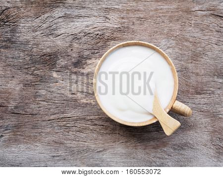 Top view cup of yogurt or sour cream with spoon on old wooden background with copy space