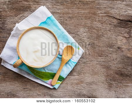 Top view cup of yogurt or sour cream and spoon on cloth plate or wooden background with copy space