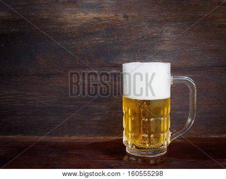 Single cold glass of beer on wooden background with copy space