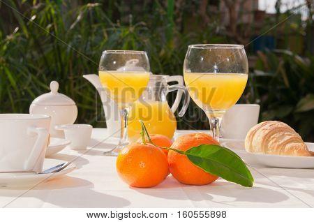 Al fresco breakfast table setting. Focus on oranges
