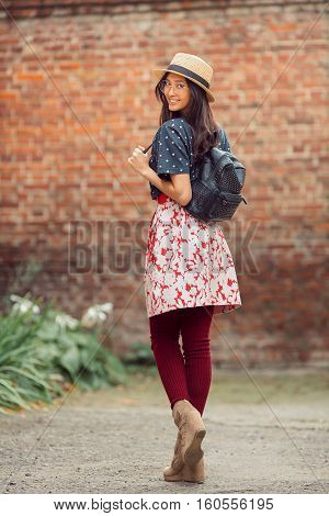Asian student girl back to school university. Beautiful woman holding straps of backpack in brick wall background. Mixed race student girl on university college campus park smiling happy and looking at camera.