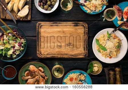 Chopping board risotto with cherry tomatoes basil and parmesan cheese roasted chicken legs snacks and and white wine on a dark wooden table top view
