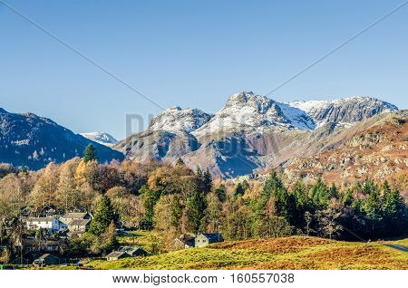 The Langdale Pikes over the village of Elterwater, Langdale, English Lake District, UK on sunny day with blue skies.