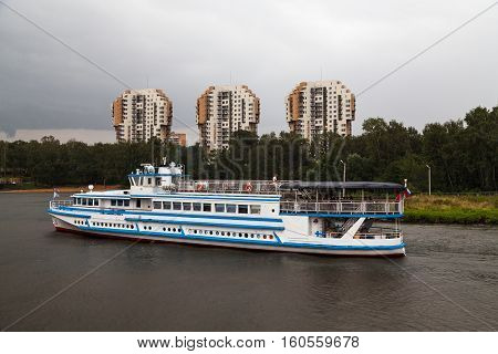 Cruise ship sets sail on the river by high-rise buildings and trees