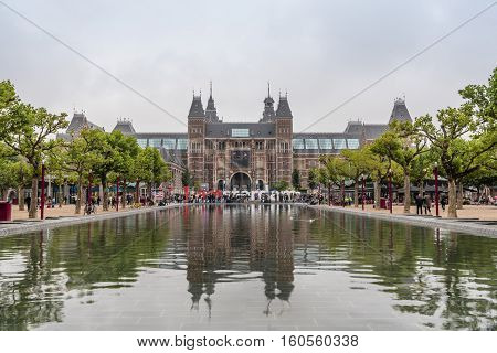 Amsterdam Netherlands - August 2 2016: Rjksmuseum in Amsterdam and reflections on pond a cloudy day. It´s a Dutch national museum dedicated to arts and history. It includes masterpieces by Rembrandt Hals and Vermeer.