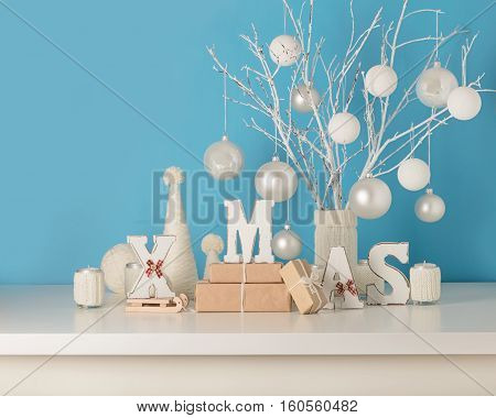 Vase in white knitted cover with white branches and Christmas toys. Candle holders in knitted covers with candles. Christmas tree made from white yarn. Wooden letters XMAS.
