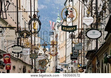 SALZBURG AUSTRIA - AUGUST 21 2016: Famous historical street Getreidegasse with multiple advertising signs. Salzburg old town was listed as a UNESCO World Heritage Site in 1997.