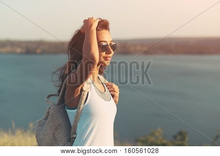 Hiker woman with backpack walking outdoors in summer at sunset . Beautiful latin young woman with windy hair