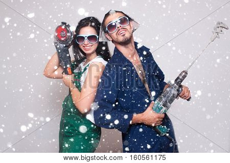 love winter christmas people concept- Male and female construction workers family happy interior new renovation young over snow background