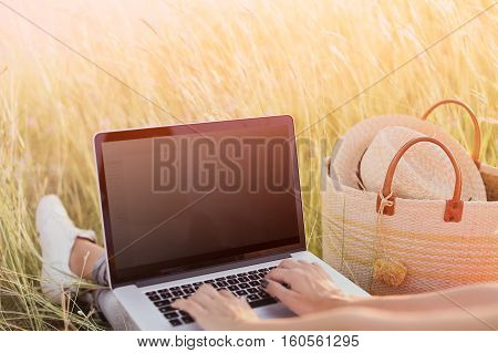 Closeup of woman's hands keyboarding on laptop with blank copy space screen for your advertising content. Girl with computer in the field