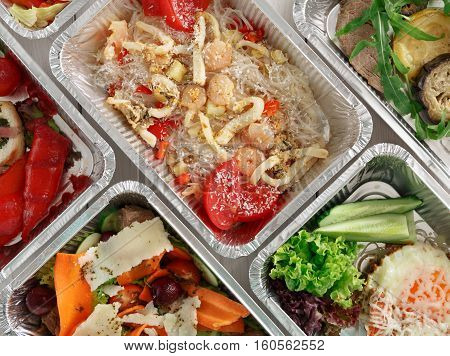 Healthy food background. Take away of natural organic food in foil boxes. Fitness nutrition, meat, rice vermicelli, vegetable salads and eggs. Top view, flat lay.