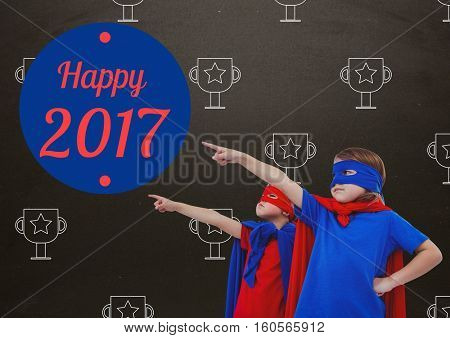 Composite image of children in super hero costumes pointing at new year greeting quotes