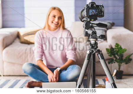 Joyful young female blogger is sitting near her laptop and smiling. Focus on screen camera