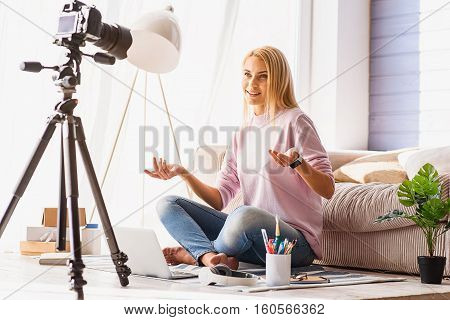 Lets talk about important things. Happy female blogger is looking at camera and smiling. She is sitting on floor near couch and laptop