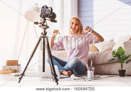 Happy young female blogger is giving thumbs up and posing to camera. She is sitting on flooring at home and smiling