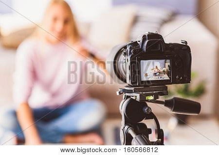 Young woman is blogging at home. Focus on camera screen