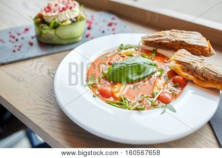 food, dinner, haute cuisine and cooking concept - plate of delicious gazpacho soup, sandwich and salad at restaurant