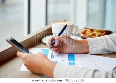 business, people, technology and lifestyle concept - woman with smartphone chart at cafe