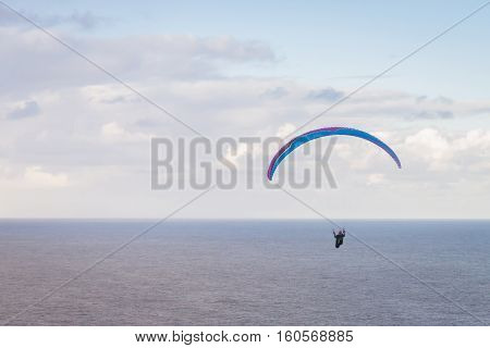 Hang glider enjoying winds high above the Pacific Ocean in Hawaii