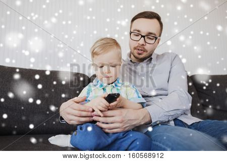 family, childhood, fatherhood, technology and people concept - happy father helping little son with remote control and watching tv at home over snow