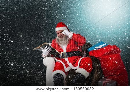 Santa reading bible with sack of christmas present beside him against snowflake pattern