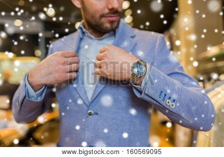 sale, shopping, fashion, style and people concept - close up of young man trying jacket at clothing store over snow