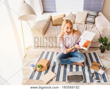 These are wonderful cosmetic products. Excited young woman is sitting on floor near sofa and holding open gift box. She is looking at camera and smiling