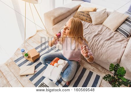 Top view of serene girl is enjoying scent of cologne. She is sitting on floor in living room and carrying box of cosmetic products
