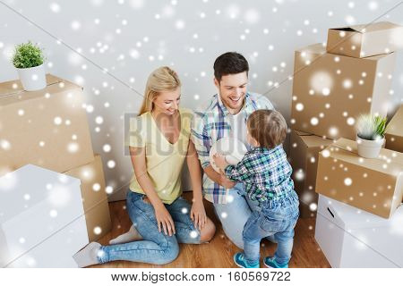 mortgage, people, housing, moving and real estate concept - happy family with boxes playing ball at new home over snow
