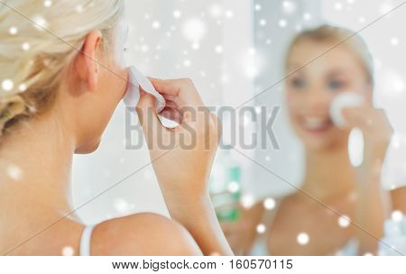 beauty, skin care and people concept - close up of smiling young woman cleaning her face with cotton disc and lotion at bathroom over snow