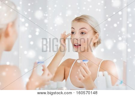 beauty, vision, eyesight, ophthalmology and people concept - young woman putting on contact lenses at mirror in home bathroom over snow