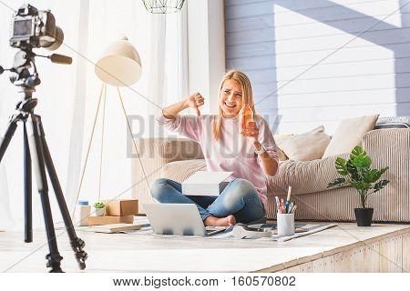 This show gel is bad. Young woman is showing thump down and looking at camera with dissatisfaction. She is sitting at home and recording blog video