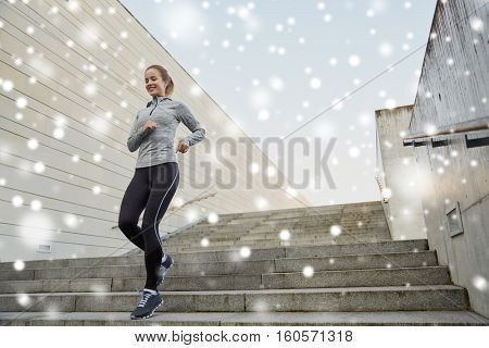 fitness, sport, people and healthy lifestyle concept - happy sporty woman running downstairs in city over snow