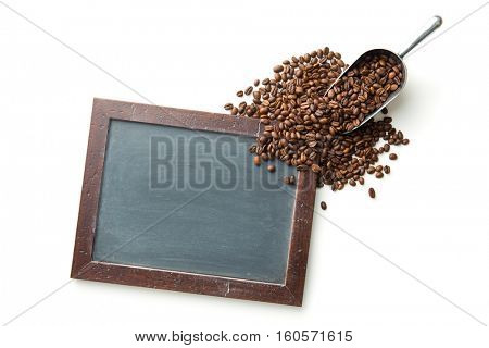 Chalkboard and coffee beans in metal scoop isolated on white background. Top view.