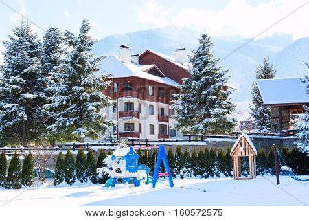 Street view with wooden chalet, snow mountains landscape panorama in bulgarian ski resort Bansko, Bulgaria