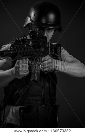Warfare, paintball sport player wearing protective helmet aiming pistol ,black armor and machine gun