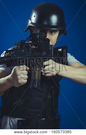 Riot, paintball sport player wearing protective helmet aiming pistol ,black armor and machine gun