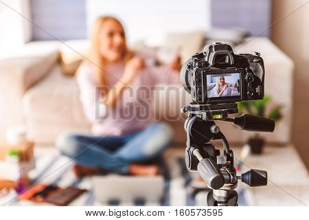 Cheerful female blogger is touching brush to blusher and smiling. Focus on camera