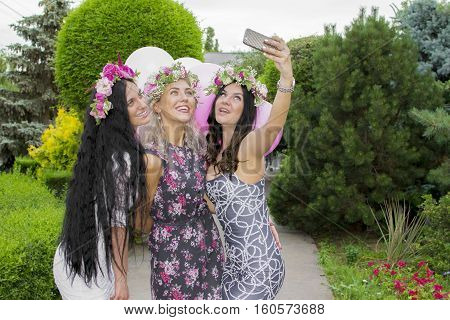 Summer Outdoor Portrait Of Three Friends Fun Girls Taking Photos With A Smartphone At Bright Sunset