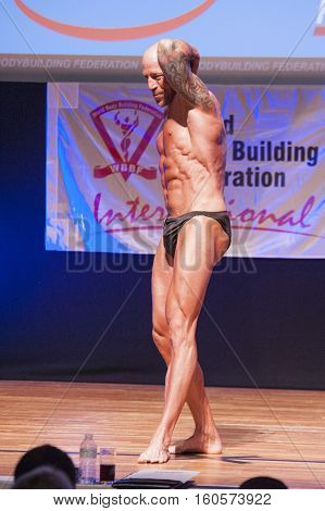 MAASTRICHT THE NETHERLANDS - OCTOBER 25 2015: Male bodybuilder Erik Stobbe flexes his muscles and shows his best physique in a abdominal and thighs pose on stage at the World Grandprix Bodybuilding and Fitness of the WBBF-WFF