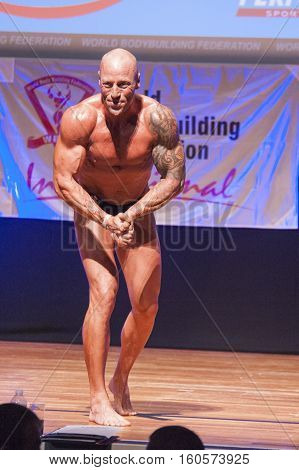 MAASTRICHT THE NETHERLANDS - OCTOBER 25 2015: Male bodybuilder Erik Stobbe flexes his muscles and shows his best physique in a most muscular pose on stage at the World Grandprix Bodybuilding and Fitness