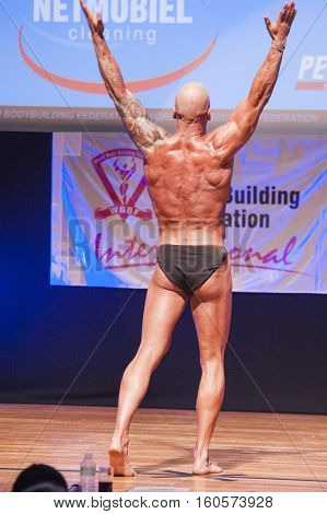 MAASTRICHT THE NETHERLANDS - OCTOBER 25 2015: Male bodybuilder Erik Stobbe flexes his muscles and shows his best physique in a back pose on stage at the World Grandprix Bodybuilding and Fitness of the WBBF-WFF