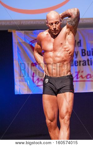 MAASTRICHT THE NETHERLANDS - OCTOBER 25 2015: Male bodybuilder Erik Stobbe shows his best abdominal and thighs pose at the World Grandprix Bodybuilding and Fitness of the WBBF-WFF