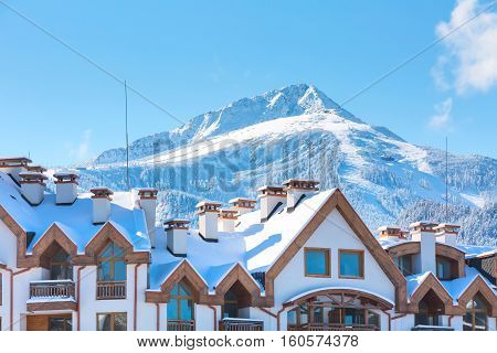Wooden chalet, houses and snow mountains landscape, ski slopes panorama in bulgarian ski resort Bansko, Bulgaria